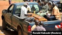 Une famille ougandaise est assise à côté du cercueil d'un parent décédé dans une camionnette à l'hôpital Mulago, à Kampala le 13 juillet 2010.