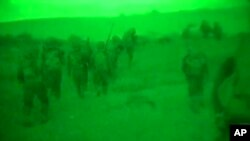 Imágen de video a través de un visor nocturno divulgado por el ejército israelí que muestra tropas de Israel caminando en Gaza.