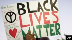 """FILE - А protester holds up a sign reading """"Black Lives Matter,"""" with the names of black men killed by police, during a rally, in Miami, Florida, Dec. 5, 2014. Albright College students in Pennsylvania have been criticized for lampooning the movement in a video."""