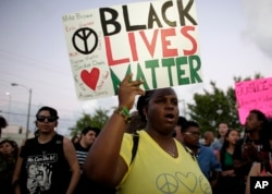 "FILE - Desiree Griffiths holds up a sign saying ""Black Lives Matter,"" with the names of Michael Brown and Eric Garner, two black men killed by police, during a protest in Miami, Florida, Dec. 5, 2014."