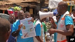 FILE - Health workers teach people about the Ebola virus and how to prevent infection in Conakry, Guinea, March 31, 2014.