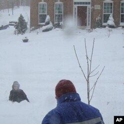 A man shovels snow while a child plays in his yard in freezing temperatures, Springfield, Virginia, 31 Jan 2010