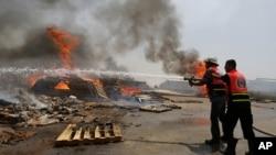 Bomberos palestinos intentan extinguir las llamas en una terminal de carga en Karni, entre Israel y Gaza, luego de ser bombardeada por tanques israelíes.