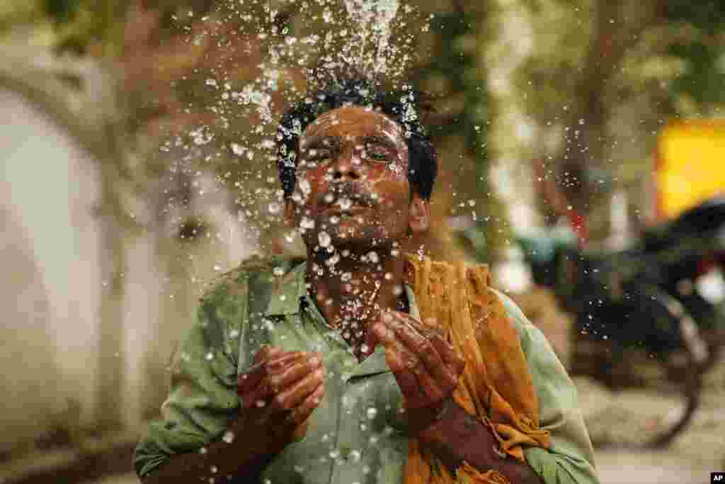 A worker splashes water to cool himself off on a hot summer afternoon in Prayagraj, Uttar Pradesh, India.
