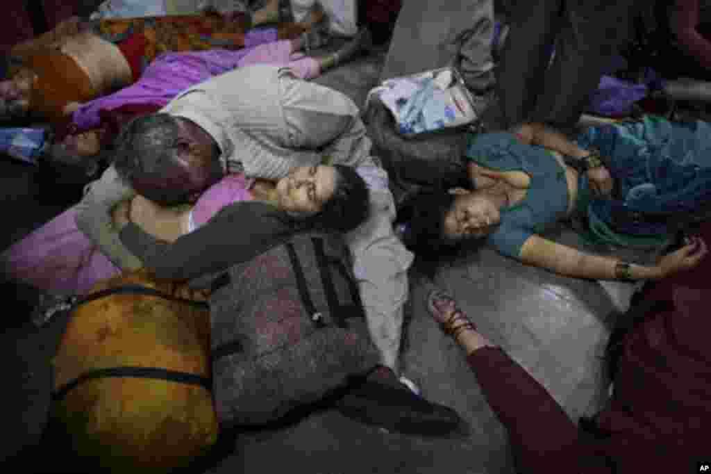 Seorang suami menangis sambil memeluk tubuh isterinya yang menjadi korban tewas akibat terinjak-injak di stasiun Allahabad, India hari Minggu (10/2).