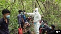 تھائی لینڈ کے فوجی میانمار سے آنے والے تارکین وطن کا کرونا وائرس کے لیے معائنہ کرتے ہوئے۔ فائل فوٹو
