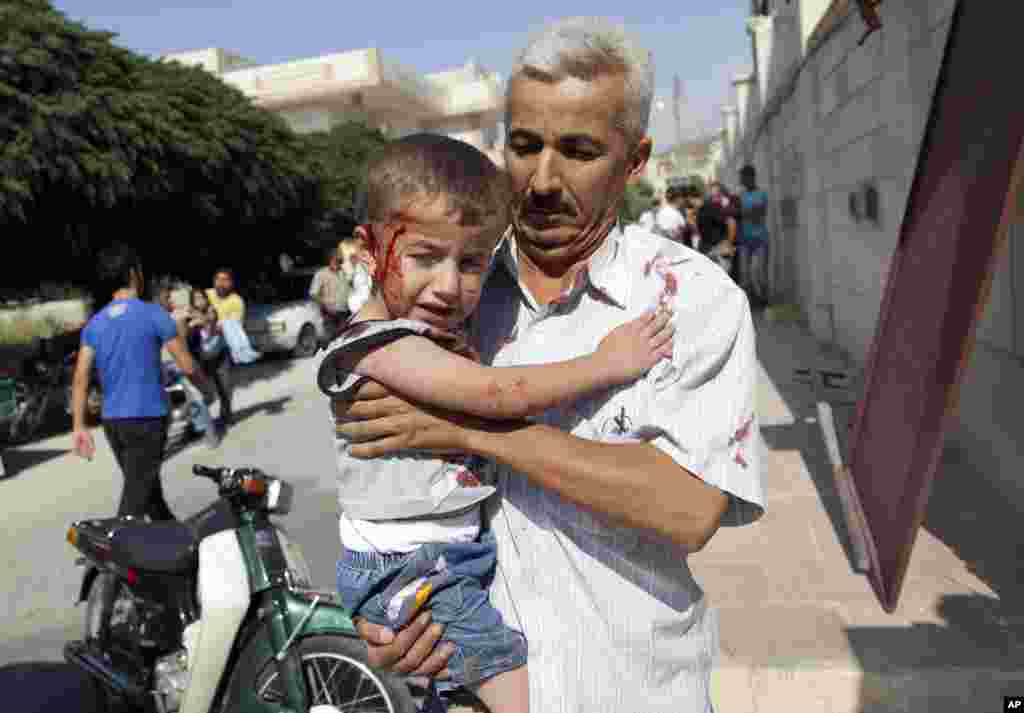 A Syrian man carries an injured child to a field hospital after an air strike hit homes in Azaz on the outskirts of Aleppo, August 15, 2012.