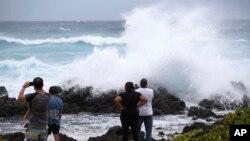 Dad sheedda ka eegaya dabeylo garaacaya mowjadaha badda xeebta Wawamalu Beach, Aug. 24, 2018, in Waimanalo, Hawaii.