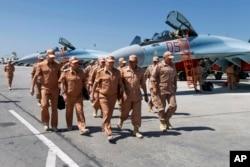In this file photo taken June 18, 2016, Russian Defense Minister Sergei Shoigu, center, visits the Hemeimeem air base in Syria