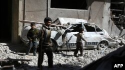 Syrian children walk through the debris in the rebel-held area of Douma, east of the capital Damascus, following reported airstrikes by regime forces, March 13, 2015.
