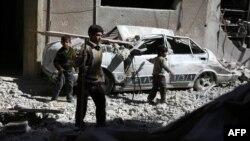 Trẻ em Syria đi trên những mảnh vỡ sau cuộc không kích của phe chính phủ, trong khu vực do phe nổi dậy chiếm giữ ở Douma, phía đông thủ đô Damascus, 13/3/2015.