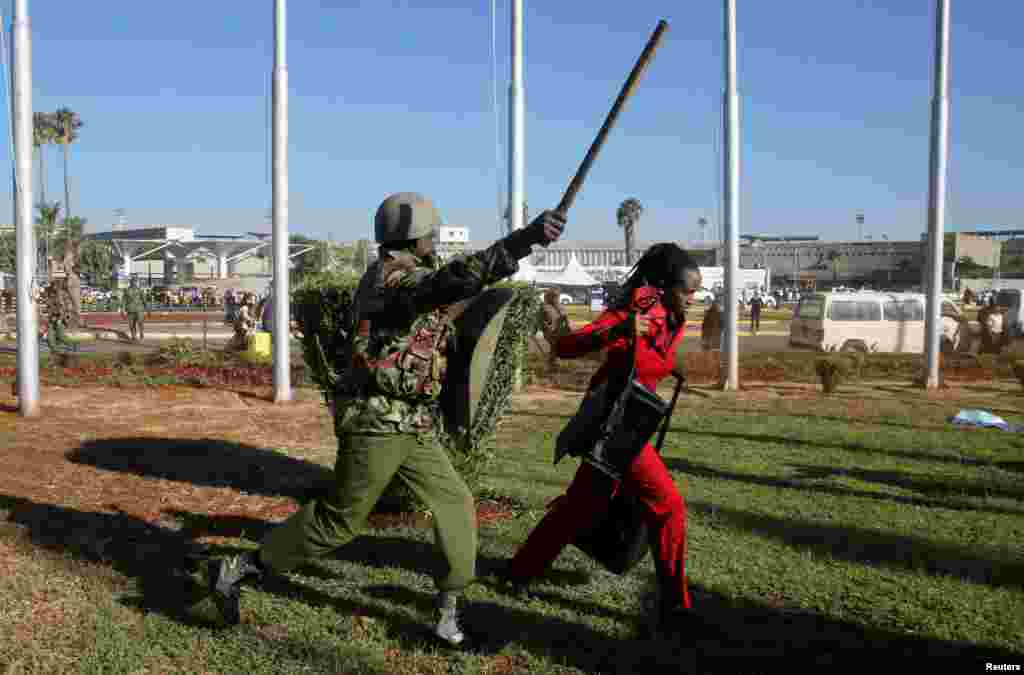 A Kenya Airways worker is dispersed by riot police at the Jomo Kenyatta International Airport during a labor dispute that grounded flights near Nairobi.