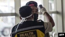 Seorang petugas memeriksa seorang penumpang yang tiba di Bandara Internasional Juanda di Sidoarjo, Jawa Timur, 30 Januari 2020. (Foto: AFP)