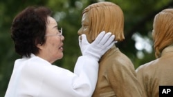 "In this Aug. 14, 2019, file photo, Lee Yong-soo, who was forced to serve for the Japanese troops as a sex slave during World War II, touches the face of a statue of a girl symbolizing ""comfort women"" during its unveiling ceremony in Seoul, South Korea. (AP Photo)"