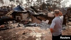 Cư dân đứng nhìn những gì còn sót lại của căn nhà bị thiêu rụi ở Blue Mountains, ngoại ô Winmalee, ngày 21/10/2013.