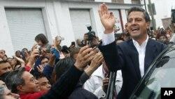 Enrique Pena Nieto (kanan), yang diperkirakan akan memenangkan pilpres Meksiko, melambai kepada para pendukungnya, Minggu (1/7).