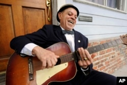 """Musician """"Deacon"""" John Moore, 74, holds his guitar in New Orleans, Louisiana, April 12, 2016."""