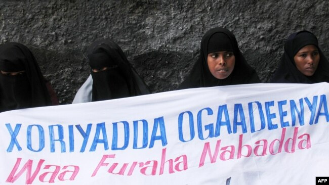 """FILE - Ogaden National Liberation Front activists hold a banner in Mogadishu that reads, """"The Ogaden freedom is the key to peace in the Horn of Africa,"""" during a ceremony that marked the organization's 22nd anniversary in Somalia, Aug. 15, 2006."""
