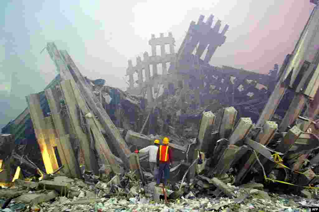 (FILE)Rescue workers survey damage to the World Trade Center 11 September, 2001 in New York. Two planes controlled by hijackers crashed into the twin towers of the center destroying the buildings. At almost the same time, another hijacked plane flew into the Pentagon in Washington, DC. AFP PHOTO Doug KANTER (Photo by DOUG KANTER / AFP)