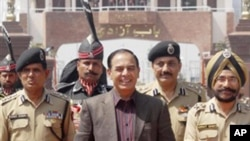 Pakistan's Interior Secretary Qamar-uz-Zaman Chaudhry walks with Indian Border Security Force officers as he arrives on the Indian side of the border at Wagah, India, March 27, 2011