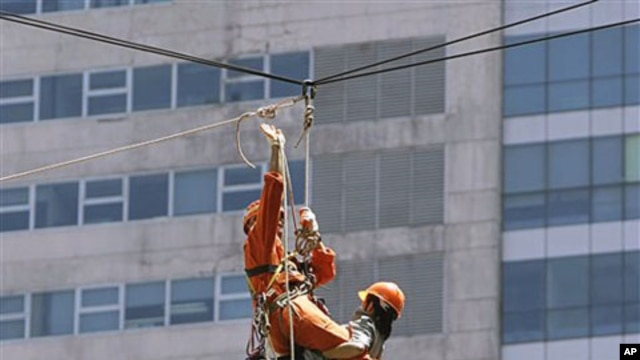 Rescuers carry people acting as victims as they rappel down a high-rise building during the National Earthquake Drill at the Ortigas commercial center as part of a disaster preparedness effort in suburban Pasig City, east of Manila, Philippines, June 2010