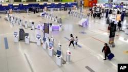 FILE - Travelers walk through the nearly empty JetBlue terminal at Logan Airport on Nov. 20, 2020, in Boston, Massachusetts. (AP Photo/Michael Dwyer)