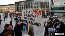 A person holds up a placard reading 'The sex mob scandal has a background' prior to a Patriotic Europeans Against the Islamisation of the West (PEGIDA) demonstration march in front of the main train station in Cologne, Germany, Jan. 9, 2016.