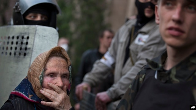 An elderly woman watch as a group of pro-Russian demonstrators storm the military Prosecutor's Office in Donetsk, Ukraine,  May 4, 2014.