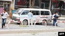 Các phóng viên đứng bên cạnh chiếc xe bị dính nhiều mảnh đạn trong vụ tấn công ở Kabul, ngày 13/9/2011