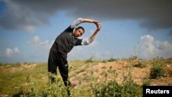 Palestinian Olympic runner Nader Al-Masri stretches near his house in Beit Hanoun in the northern Gaza Strip, April 10, 2014.