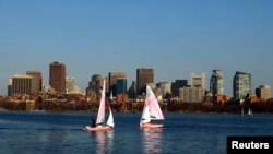 FILE - Collegiate sailors practice on the Charles River in front of the Boston skyline in Cambridge, Massachusetts, March 20, 2012.