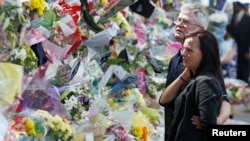 Ian Rigby (R), the stepfather of murdered British soldier Lee Rigby, and Sarah McClure look at floral tributes left at the scene of his killing in Woolwich, May 26, 2013.