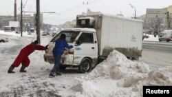 Men push a vehicle after a heavy snowfall in Moscow, Russia, Feb. 5, 2018.