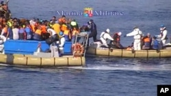 This image taken from video provided by the Italian Navy (Marina Militare) Saturday, Aug. 15, 2015, shows an Italian Navy RIB approaching a fishing boat crowded with migrants off the coast of Libya.