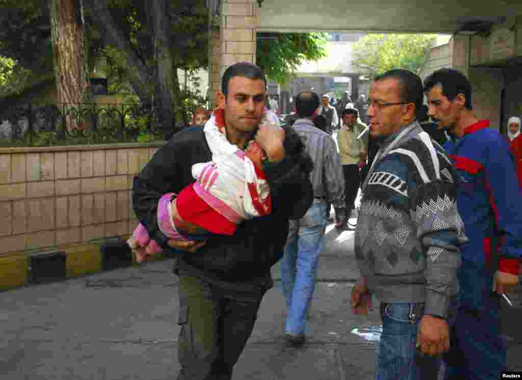 A man carries an injured child after a bomb explosion in front of the al-Hejaz train station in central Damascus, Nov. 6, 2013. (SANA)