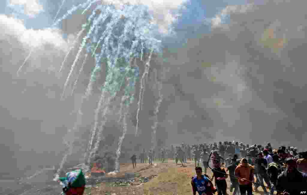 Palestinians run for cover from tear gas fired by Israeli forces near the border between the Gaza strip and Israel east of Gaza City as Palestinians protest over the inauguration of the U.S. embassy following its move to Jerusalem.