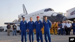 The STS- 135 crew stands next space shuttle Atlantis shortly after landing at the Kennedy Space Center at Cape Canaveral, Florida, July 21, 2011