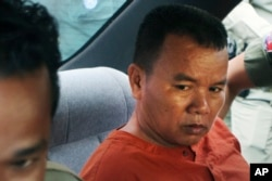 FILE - Yem Chrin, an unlicensed medical practitioner, is escorted by prison guards in Battambang province, northwest of Phnom Penh, Cambodia, Dec. 3, 2015.