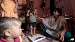 FILE - A volunteer weighs a malnourished child at the Apanalay center in Mumbai, India. A new study indicates that in the same way that lack of food can harm children, violence, deprivation and neglect are also damaging their brain circuitry.