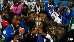 Les joueurs de TP Mazembe célèbrent avec le trophée leur victoire sur Supersport United au terme de la finale retour de la Coupe de la CAF, au stade Lucas Moripe, à Atteridgeville, Pretoria, 25 novembre 2017.