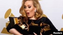 Singer Adele holds her six Grammy Awards at the 54th annual Grammy Awards in Los Angeles, California on Feb. 12, 2012.
