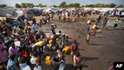 FILE - A year after fighting broke out in South Sudan, people gathered around a water truck to fill containers at a U.N. compound in Juba that had become home to thousands of displaced people, Dec. 29, 2013.