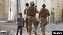 Seorang pria berjalan melewati tentara koalisi yang dipimpin Saudi di Aden, Yaman, 26 September 2015 (Foto: dok).