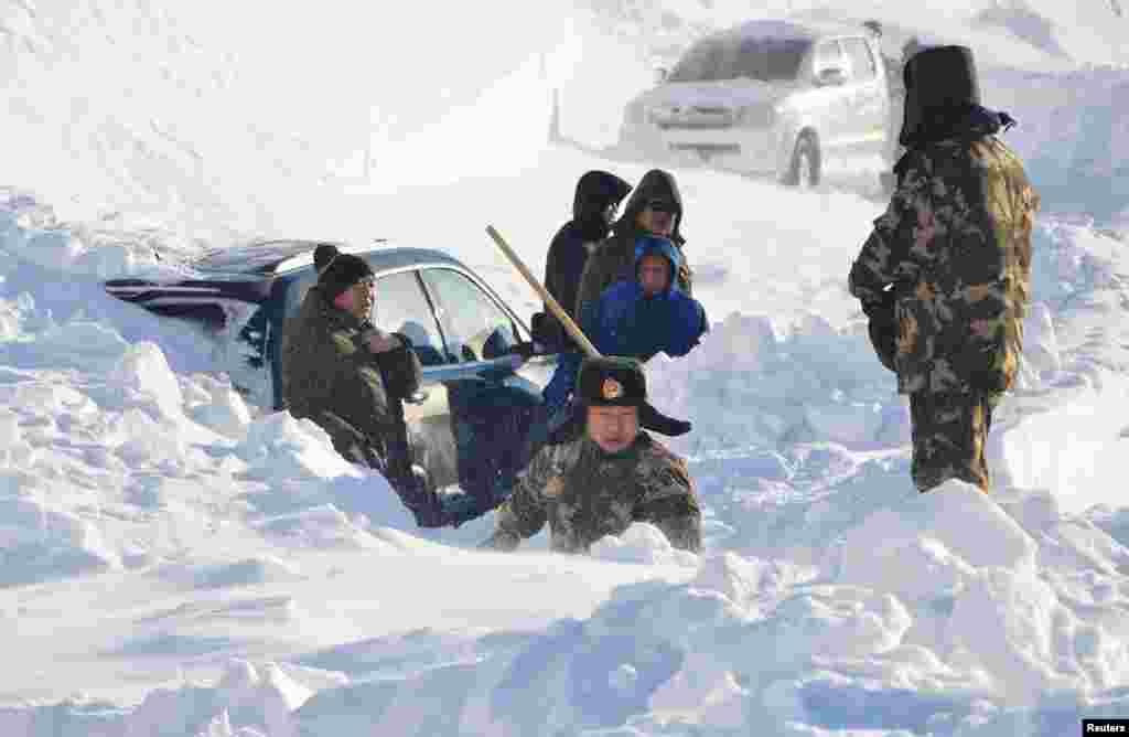 Police digging out a car trapped in a snow slide in Altay, Xinjiang Uighur Autonomous Region, China, Jan. 3, 2016.