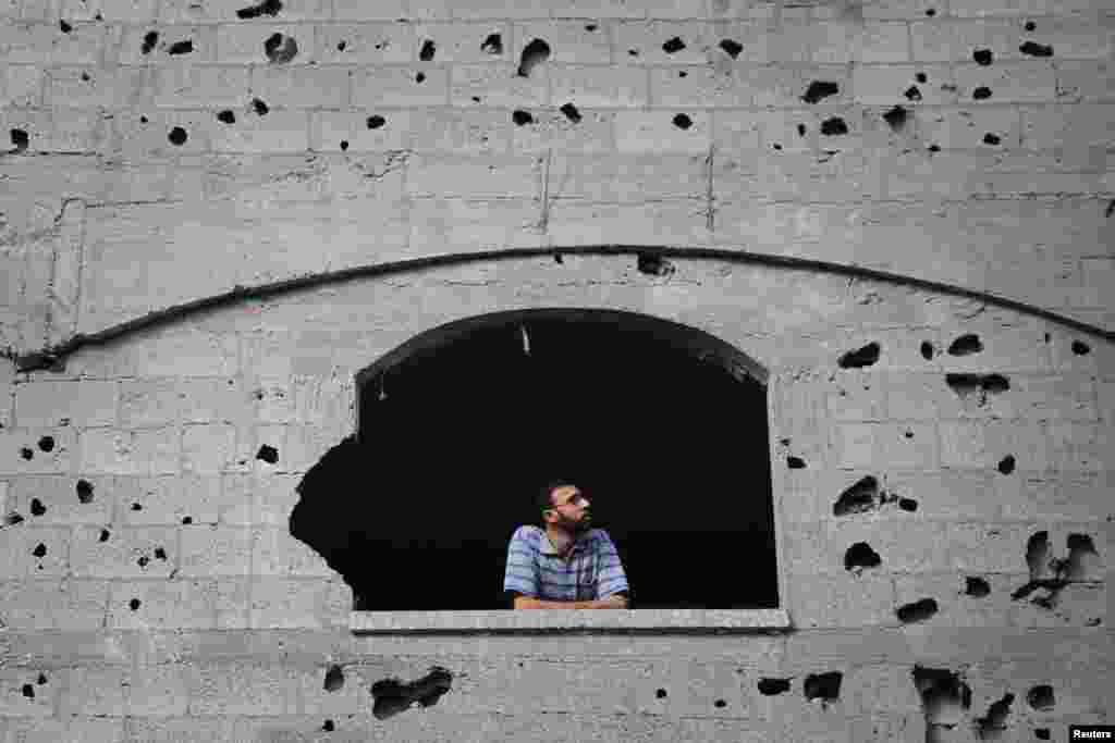 A Palestinian man looks through a window scarred with shrapnel from a neighbouring building that police said was hit by an overnight Israeli air strike, in Jabaliya in the northern Gaza Strip, July 24, 2014.