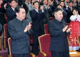 FILE - Kim Jong-Un (R) applauding at the Unhasu orchestra concert at the People's Theatre in Pyongyang, as his uncle,Jang Song-Thaek, looks on.