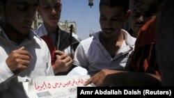 El-Ahram gazetesinin manşet haberini okuyan Mısırlılar
