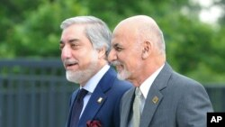 FILE - Afghanistan's President Ashraf Ghani, right, and Chief Executive Abdullah Abdullah arrive for sessions of the second day of the NATO Summit, in Warsaw, Poland, July 9, 2016.