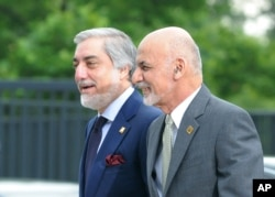 FILE - Afghanistan's President Ashraf Ghani, right, and Chief Executive Abdullah Abdullah arrive for sessions of a NATO Summit, in Warsaw, Poland, July 9, 2016.