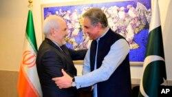 Menlu Iran Mohammad Javad Zarif (kiri) berjabat tangan dengan Menlu Pakistan Shah Mehmood Qureshi sebelum pertemuan di Islamabad, hari Jumat (24/5).